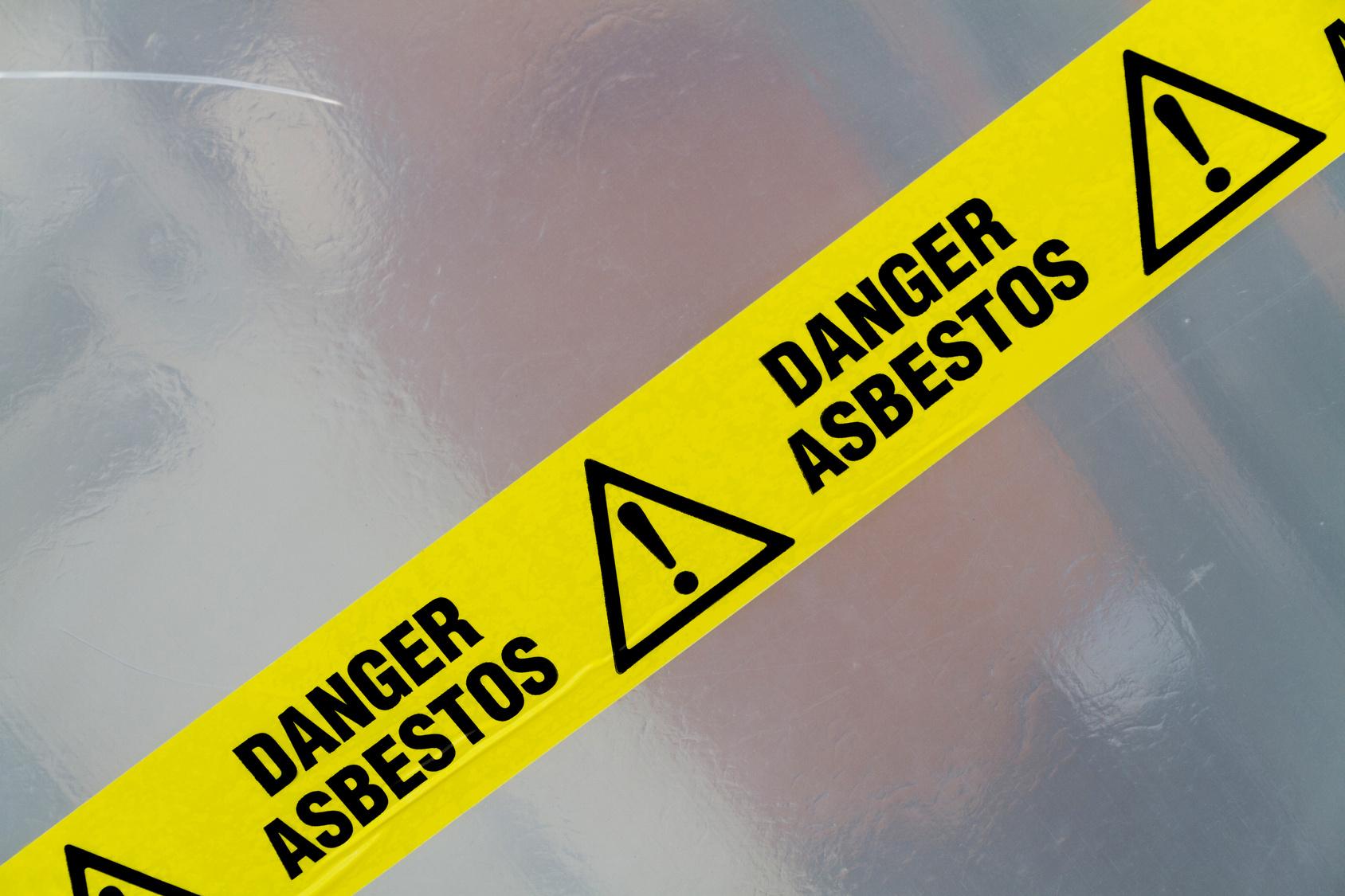 Danger Asbestos yellow warning tape close up
